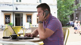 Young man typing on laptop answers phone call, slider shot right stock footage