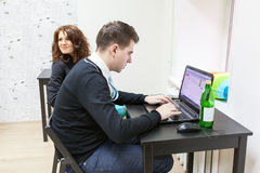Young man typing with laptop and girlfriend sitting near Stock Photography