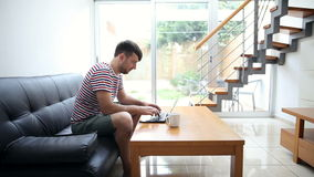 Young man typing on laptop at home. Young handsome man typing on laptop and drinking coffee at modern cozy home stock video footage