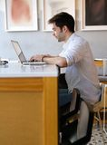 Young man typing on laptop at internet cafe Stock Image