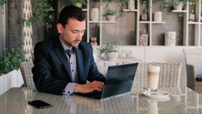 Young man typing on a laptop. Latte is on the table next to a man in a cafe. A man sitting in a restaurant. A handsome man sitting at a table in a restaurant stock footage