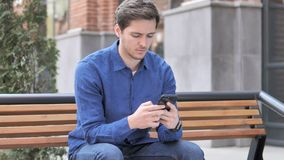 Young Man Typing Message on Smartphone, Sitting Outdoor on bench. 4k high quality, 4k high quality stock video footage
