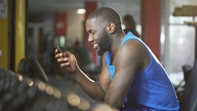Young man typing message on smartphone with smile on face, break during workout. Stock footage stock footage