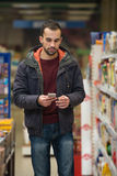 Young Man Typing On Mobile Phone At Supermarket Royalty Free Stock Image