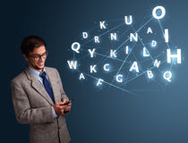Young man typing on smartphone with high tech 3d letters comming Royalty Free Stock Image