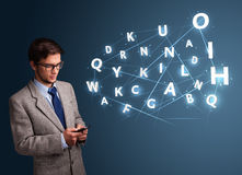 Young man typing on smartphone with high tech 3d letters comming Royalty Free Stock Images