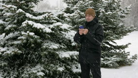 Young man typing a sms message on the phone in the winter snowy forest. Big snowfall. He smiles and speaks the written. Young man typing a sms message on the stock footage
