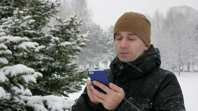 Young man typing a sms message on the phone in the winter snowy forest. Big snowfall. He smiles and speaks the written. Young man typing a sms message on the stock video