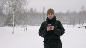 Young man typing a sms message on the phone in the winter snowy forest. Big snowfall. He smiles and speaks the written. Young man typing a sms message on the stock video footage