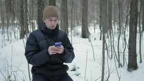Young man typing a sms message on the phone in the winter snowy forest. He smiles and speaks the written. Young man typing a sms message on the phone in the stock video