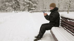 Young man typing a sms message on the phone in the winter snowy park. He smiles and speaks the written. Young man typing a sms message on the phone in the stock footage