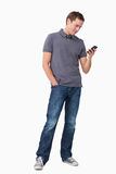 Young man typing text message on his cellphone Stock Photos