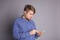 Young man typing text message on his cellphone against a gray background.  Royalty Free Stock Photos