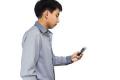 Young man typing text message on his cellphone against a white b. Ackground Stock Photography