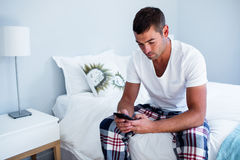 Young man typing a text message on phone. In bedroom Royalty Free Stock Photos