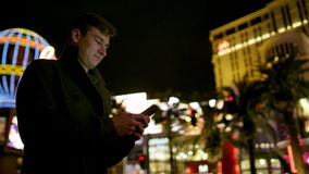 Young man is typing a text message on a street. Young man is typing a text message by using his smartphone while standing on a sidewalk in Vegas at night time stock video footage