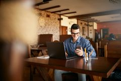 A young man typing a text on mobile modern smartphone. Hipster holding a modern phone and writing a phone message. Smiling young businessman in glasses looking Royalty Free Stock Photography