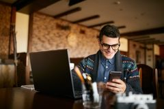 A young man typing a text on mobile modern smartphone. Hipster holding a modern phone and writing a phone message. Smiling young businessman in glasses looking Stock Photos