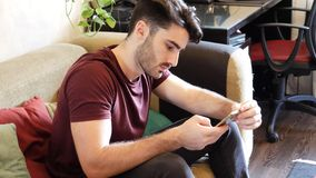 Young man typing and using cell phone Royalty Free Stock Image