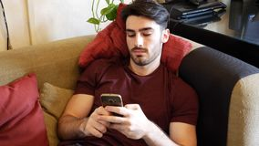 Young man typing and using cell phone Royalty Free Stock Photo