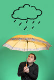 Young Man with umbrella looking up on a rain cloud