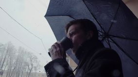 Young man with umbrella standing under snowfall drinking coffee from plastic cup. Young man with umbrella standing under a snowfall with pleasure drinking hot stock video footage