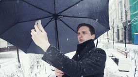Young man with umbrella under snowfall making selfie photo using smartphone. Close-up of young man with umbrella under snowfall making selfie photo on smartphone stock video footage