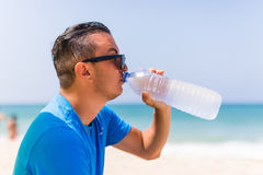 Young man under green solar umbrella drink water from cooler on beach Stock Photo