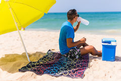 Young man under green solar umbrella drink water from cooler on beach. Young men under green solar umbrella drink water from cooler on beach. Summer time Royalty Free Stock Photography
