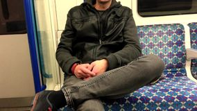 Young man in underground. Young white man sitting in underground rail in London stock footage