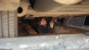 Young man underneath a car unscrewing details from under tray. Close up stock video footage