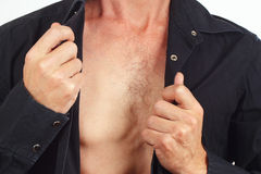 Young man undresses his black shirt closeup Royalty Free Stock Images