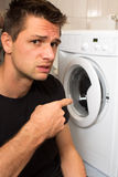Young man unhappy with washing mashine. And pointing at it Stock Photography