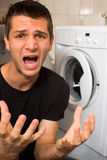 Young man unhappy with washing mashine. And angry Royalty Free Stock Photography