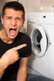 Young man unhappy with washing mashine Royalty Free Stock Image