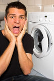 Young man unhappy with washing mashine. And frustrated Stock Image