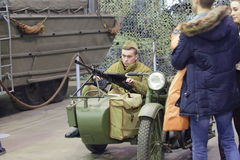 Young man in uniform of Red Army with machine gun sits in motorcycle stroller Royalty Free Stock Photography