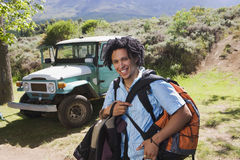 Young man unloading parked jeep at start of camping holiday, carrying rucksacks, smiling, portrait Stock Image