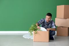 Young man unpacking box indoors. Moving into new house royalty free stock photography