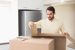 Young man unpacking boxes in kitchen Royalty Free Stock Photo