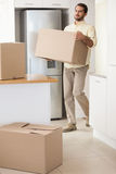 Young man unpacking boxes in kitchen Stock Photography