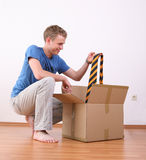 Young man unpacking cardboard box Stock Photo