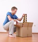 Young man unpacking cardboard box stock photo