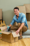 Young man unpacking carton boxes Stock Image