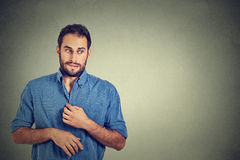 Young man in unpleasant, awkward situation, playing nervously with hands. Embarrassment Stock Photography