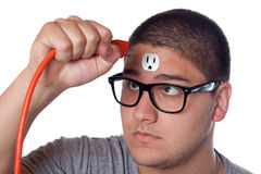 Young Man Unplugged. Conceptual image of a young man holding an electrical chord unplugged from the outlet on his forehead stock image