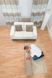 Young Man Unrolling Carpet Royalty Free Stock Photo