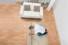 Young Man Unrolling Carpet Royalty Free Stock Photos