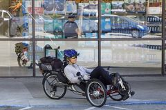 Young man on an unusual bike. Milpitas, California, United States - March 26, 2016: A young man riding a unusual tricycle. Behind the big shop windows Stock Photography