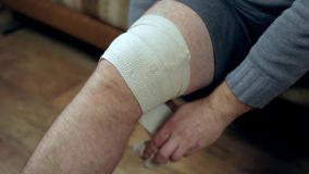 Young man unwrapping his knee injury with elastic bandage closeup stock video footage